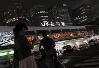 仏印から東京へ引き揚げてきたゆき子は品川で下車した。<ホームは薄汚れた人間でごった返している>。現在の夜のJR品川駅前=東京都港区で、佐々木順一撮影