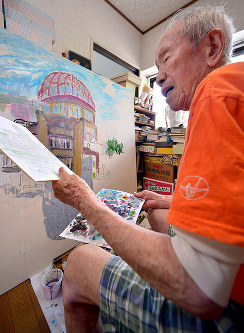 Hiroshi Hara works on a painting of the atomic bomb dome, while referring to a previous painting, in Hiroshima's Aki Ward, on July 17, 2017. (Mainichi)
