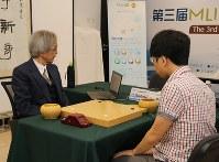 パソコンの画面を見ながら申旻〓五段(右)との対局に臨む、Zenチーム代表の加藤英樹さん(左)=日本棋院提供