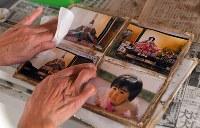 豪雨で自宅から流されたアルバムが川の下流で発見され、この日持ち主に届けられた。「福岡市で暮らす中学生の孫が小さかったころの写真。よく見つかったね」と祖母は1枚1枚丁寧にぬぐっていた=福岡県朝倉市杷木林田で2017年8月1日、森園道子撮影