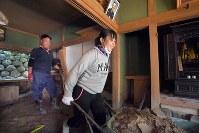 自宅に流れ込んだ土砂を父の慎也さん(39)と一緒に片付ける高校1年の藤本遥風(はるか)さん。家が流されるなど大きな被害を受けた友達も多い。「まず地域が復興してほしい。行方不明の人も見つかってほしい。被災者は元気がないので、みんなを笑顔に、元気にしてくれる人が朝倉に来てくれたらいいな」=福岡県朝倉市杷木星丸で2017年8月2日、森園道子撮影