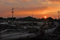 夕日に浮かぶ市街地に残る流木=福岡県朝倉市山田で2017年8月1日、森園道子撮影