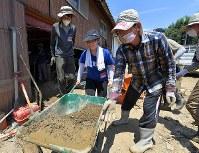 大人に助けられながら、泥を載せた重い一輪車を押す中学1年の三好弥鈴(みすず)さん(中央)。「初めてボランティアに来ましたが、思っていたよりも砂ぼこりとにおいがきつい。被災した方たちはしんどいのにそう言わず、お互いに助け合って生きている。すごいなあ」=福岡県朝倉市杷木寒水で2017年7月30日、森園道子撮影