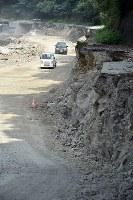 濁流にのまれ、崩壊した道路(右上)の下につくられた仮設の道=福岡県朝倉市で2017年7月31日、森園道子撮影