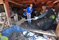 「あっ、農機具らしきものが見えてきた」。農作業小屋の中の泥をかき出すボランティアたち=福岡県朝倉市杷木寒水で2017年7月30日、森園道子撮影