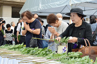 献花台に花を供え、犠牲者の冥福を祈る参列者ら=広島市中区の同市役所前広場で、大東祐紀撮影