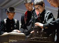 被爆前後の原爆ドームの模型を並べた展示コーナーで原爆の威力を体感する中学生たち=広島市中区の広島原爆資料館で2017年4月26日、山田尚弘撮影