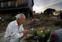 九州北部豪雨の犠牲者宅周辺などで土砂の除去作業などを手伝い、供えられた花束の前で手を合わせる男性=福岡県朝倉市で2017年8月5日午後6時57分、和田大典撮影