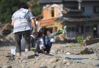 集落の犠牲者を悼んで花を手向ける住民たち=福岡県朝倉市杷木志波で2017年8月5日午前8時2分、津村豊和撮影