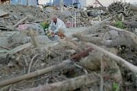 九州北部豪雨の犠牲者宅やその周辺で土砂の除去作業などを手伝った男性。ナシを供えて手をあわせた=福岡県朝倉市山田で2017年8月5日午後6時55分、和田大典撮影