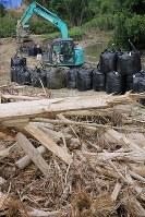 台風5号の接近に備え、川岸に積まれる土のう。作業員の男性は「台風が来るまでになんとか終わらせたい」と話した。=福岡県朝倉市山田で2017年8月5日午後2時2分、和田大典撮影