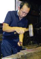 「ふくべ鍛冶」の作業場で鉄を打つ干場健太朗さん=石川県能登町で、中本泰代撮影