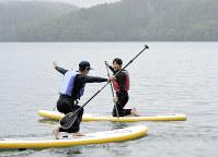 湖に浮かべたボードの上で着地の「テレマーク姿勢」を決める渡部暁斗(左)。右は永井秀昭=長野県大町市で2017年6月30日、江連能弘撮影