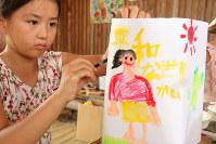 小学4年生の伊藤詩生さんは初めて「原爆の図」を見た。それまでイメージを持っていなかった戦争について「これは大変なことだ」と怖くなったという。真剣な表情で、「これからは世界が平和であるように」との願いを灯籠に込めた=原爆の図丸木美術館で2017年8月6日、岡本同世撮影