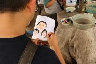 「絵心はないのですが……」と言いながら、家族の笑顔を灯籠に描く男性=原爆の図丸木美術館で2017年8月6日、岡本同世撮影