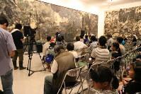 「ひろしま忌のつどい」であいさつする小寺隆幸理事長(奥)。「核兵器禁止条約は、日本が不参加のままなら絵に描いた餅だ」と日本政府に条約批准を求めた=原爆の図丸木美術館で2017年8月6日、岡本同世撮影