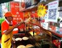 朝食を売る露店に掲げられたモバイル決済の「二次元コード」。これをスマホで読み込んで料金を支払う=中国青島市で、赤間清広撮影