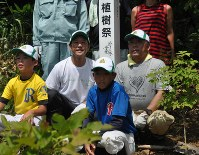 植樹したアオダモの横で記念撮影する栗山監督(左から2人目)=栗山町で