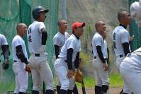 選手らと一緒に打撃練習の打球の行方を見つめる小田監督(中央)