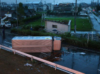 A truck lies on the road in Toyohashi, Aichi Prefecture, after being blown over by a sudden gust on the afternoon of Aug. 7, 2017. In the background are roofs whose tiles have been blown off. (Mainichi)
