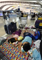 Children sleep on a sheet in the departure lobby of Kansai International Airport on the evening of Aug. 7, 2017, as they wait for flights that were cancelled due to Typhoon Noru to resume. (Mainichi)
