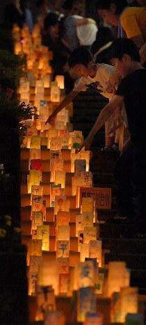 平和への願いが記されたキャンドルに見入る子どもたち=長崎市の平和公園で2017年8月8日午後8時25分、森園道子撮影