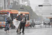 強風にあおられる人たち=JR姫路駅前で、待鳥航志撮影