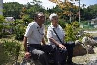 再建した自宅の庭の石に腰を下ろし、亡くなった姉の一子さんの思い出を話す大町官教さん(左)と妻キサさん=山田町大沢で