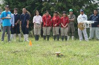生徒らにドローン操縦の手本を示す則武さん(左端)