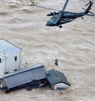 大雨で鬼怒川が決壊し、自衛隊のヘリで救助される人=茨城県常総市で2015年9月10日午後4時9分、本社ヘリから長谷川直亮撮影