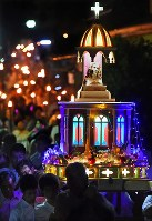 A statue of the Virgin Mary that was exposed to the atomic bombing of Nagasaki is carried toward Nagasaki's Peace Park, in the city on the evening of Aug. 9, 2017. (Mainichi)