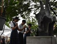 原爆犠牲者慰霊平和祈念碑に手を合わせる中学生