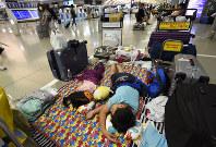 台風5号の影響で欠航が相次ぎ、出発ロビーでレジャーシートを敷いて運航再開を待つ子どもたち=関西国際空港で2017年8月7日午後8時34分、久保玲撮影