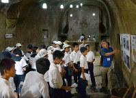 平和学習で無窮洞を訪れた長崎日大中の生徒ら。主洞の突き当たりに教壇がある