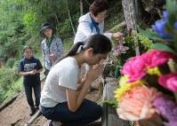 花を供えた銘標で手をあわせる遺族=群馬県上野村の御巣鷹の尾根で2017年8月12日午前9時15分、和田大典撮影