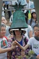 昇魂之碑の前で黙とうした後、「安全の鐘」を鳴らす人たち=群馬県上野村の御巣鷹の尾根で2017年8月12日午前10時40分、和田大典撮影
