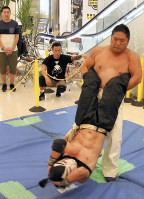 レスラーが大技を決めると、通りすがりの買い物客から歓声が上がった=和歌山市美園町で2017年8月12日、稲生陽撮影