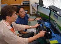 ドライブシミュレーターでの訓練に取り組む浜松市の男性(左)。右はアドバイスする建木健・聖隷クリストファー大助教=浜松市北区の同大で
