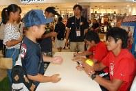ファンにサインする上野由岐子投手(右)と藤田倭投手(右から2人目)=高崎市棟高町のイオンモール高崎で