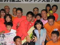 世界陸上での健闘をたたえる市民らとともに記念撮影に応じる川内優輝選手(中央)。その右下は特別ゲストの谷川真理さん=久喜市で