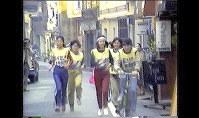 「真の男女雇用平等法を」と政府への要望書をバトンに入れ、東京都内を駅伝のように走った女性たち=映画「たたかいつづける女たち」より