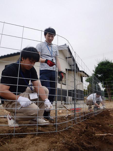 帰還住民が暮らす民家をイノシシの侵入から防ごうと、約50メートル四方の敷地を丸ごとフェンスで囲う自治体職員たち。今後効果を確認し、事業として普及できるかを検討する=福島県浪江町加倉で2017年7月27日、尾崎修二撮影