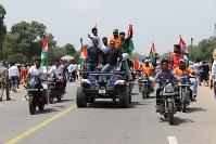 インド独立70年を祝い、国旗を掲げて街中を走る若者たち=ニューデリーで2017年8月15日、金子淳撮影