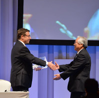 In this October 2013 file photo, then Minamata Mayor Katsuaki Miyamoto, right, shakes hands with then U.N. Environment Programme Executive Director Achim Steiner after a conference on the Minamata Convention on Mercury in the city of Kumamoto. (Mainichi)