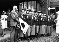 ドイツ・フリードリッヒ駅に到着し歓迎を受ける日本女子水泳選手一行。ユニホームも軍国色。左端は大会会長のレワルト博士。選手左端の日の丸を持つ女性が前畑秀子選手=ベルリンで1936(昭和11)年7月2日、高田正雄本社特派員撮影
