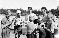 ベルリン入りする前に調整するヘルシンキで、サインを求める地元の子どもたちに囲まれる陸上女子走り高跳びの西田順子選手=フィンランドのヘルシンキで1936(昭和11)年6月、高田正雄本社特派員撮影
