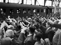 日本選手たちの君が代の合唱に合わせ、ナチス式の敬礼で出迎える人たち=ベルリンのフリードリヒ駅プラットホームで1936(昭和11)年6月、高田正雄本社特派員撮影