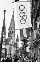 オリンピック旗の装飾とカイザー・ウィルヘルム記念教会(教会は1943年11月の英空軍の空襲で炎上し、写真の一番高い鐘塔は壊れたが、戦争を警告する記念碑として残されている)=ベルリンで1936年7月、高田正雄本社特派員撮影