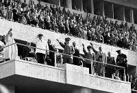表彰式の国旗掲揚で敬礼するヒトラー(中央)。スタンドの観衆も全員が立ち上がりナチス式の敬礼をしている=ベルリンのオリンピックスタジアムで1936(昭和11)年8月、高田正雄本社特派員撮影