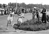 マラソンの折り返しを回る孫基禎選手は、英国のハーパー選手(左)との差をひろげ2時間29分19秒2で優勝した=ベルリンで1936(昭和11)年8月9日、高田正雄本社特派員撮影